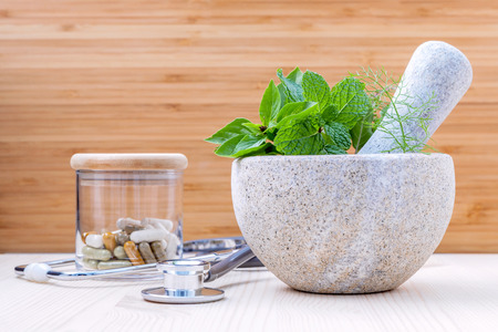 Fresh herbal leaves basil ,sage , mint ,holy basil ,fennel and capsule of herbal medicine alternative health care with stethoscope setup on wooden background. Stock Photo