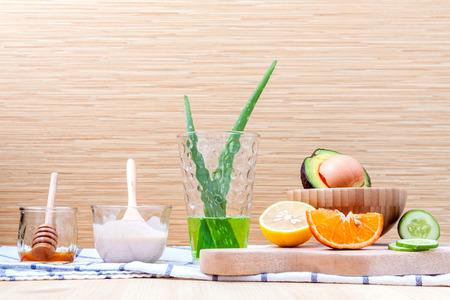 Hausgemachte Hautpflege und Körperpeeling mit natürlichen Zutaten, Avocado, Aloe Vera, Zitrone, Gurke, Orange, Apfel, Limone und Honig auf auf Holzuntergrund aufstellen.