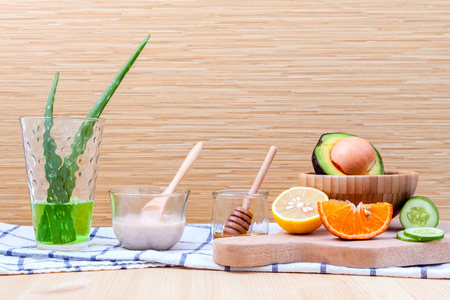 Homemade skin care and body scrub with natural ingredients avocado ,aloe vera ,lemon,cucumber ,orange and honey set up on on  wooden background. Фото со стока