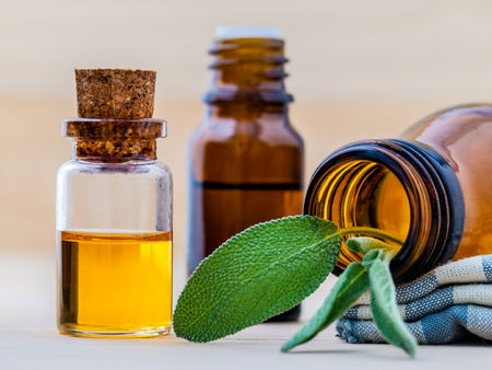odorous: Bottle of essential oil with  fresh sage leaves shallow depth of field on old wooden background. Stock Photo