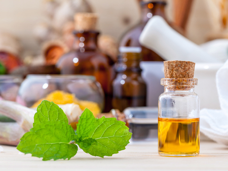 field mint: Fresh green mint and essential oil with shallow depth of field setup on wooden background .