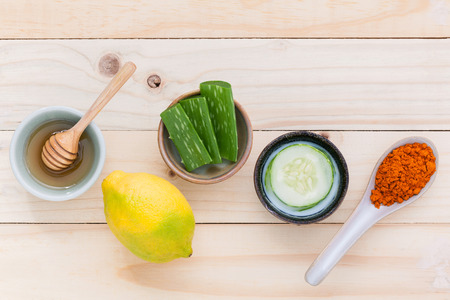 tumeric: Homemade skin care and body scrub with natural ingredients  aloe vera ,lemon,cucumber ,tumeric powder and honey set up on on wooden background. Stock Photo