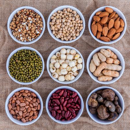 Mischbohnen, Linsen und Nüsse in der weißen Schüssel auf braunem Stoffsackhintergrund. Mungbohne, Erdnuss, Sojabohne, rote Kidneybohne, Lotussamen, Mandel, grüne Bohne, Hirse, Cashew und braune Pintobohnen.