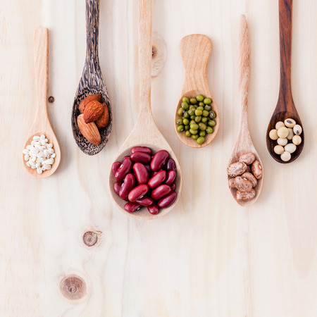 Assortment of beans and lentils in wooden spoon on wooden background. mung bean, groundnut, soybean, red kidney bean and almond. Stock Photo