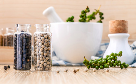 white pepper: Assorted of spice bottles condiment black pepper ,white pepper and  green pepper seeds with mortar on wooden background.