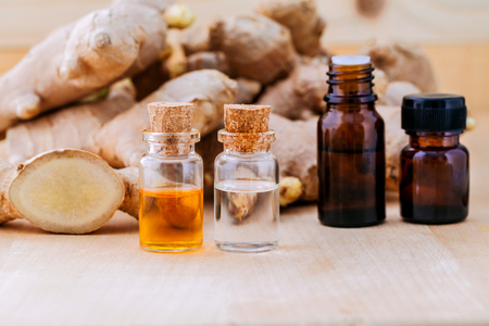 Bottles of ginger oil and ginger on wooden background with selective focus.