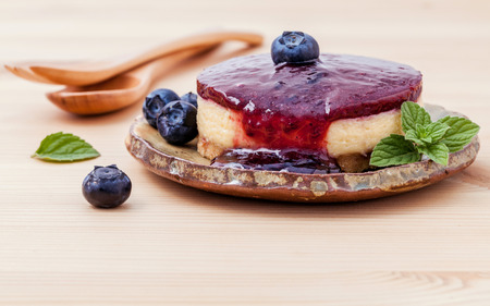 field mint: Blueberry cheesecake with fresh mint leaves on wooden background. Selective focus depth of field. Stock Photo
