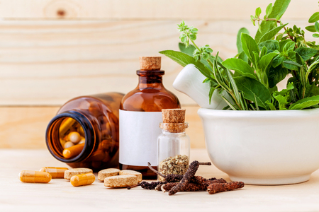 alternative health care: Alternative health care fresh herbal  ,dry and herbal capsule with mortar on wooden background. Stock Photo