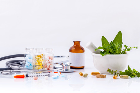 alternative health: Alternative health care concept. Fresh herbs green mint ,rosemary ,parsley ,sage and lemon thyme in laboratory glassware with stethoscope on wooden background.