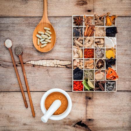 대체 건강 관리는 오래 된 목조 배경에 박격포와 나무로되는 숟가락에 나무 상자와 허브 캡슐의 다양한 중국어 허브를 건조.