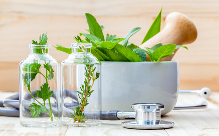 medical test: Alternative health care concept. Fresh herbs green mint ,rosemary ,parsley ,sage and lemon thyme in laboratory glassware with stethoscope on wooden background.