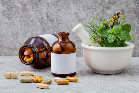 alternative health: Alternative health care fresh herbs  rosemary ,lemon thyme ,fennel ,peppermint ,basil flower and herbal capsule with mortar on stone background.