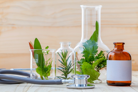 alternative health care: Alternative health care concept. Fresh herbs green mint ,rosemary ,parsley ,sage and lemon thyme in laboratory glassware with stethoscope on wooden background.