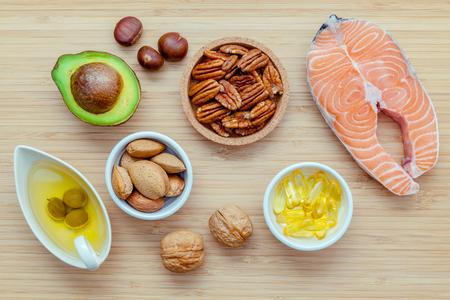 Selección de las fuentes de alimentos de ácidos grasos omega 3 y grasas no saturadas. súper alimento ricos en omega 3 y grasas no saturadas para una alimentación sana. Almendras, pacanas, avellanas, nueces, aceite de oliva, aceite de pescado, salmón y aguacate en el fondo de madera. Foto de archivo