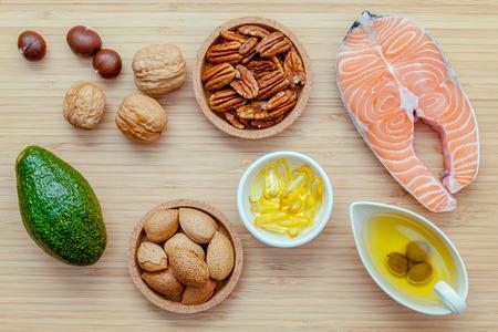 Selectie voedsel bronnen van omega 3 en onverzadigde vetten. Super eten hoge omega 3 en onverzadigde vetten voor een gezonde voeding. Almond, pecannoten, hazelnoten, walnoten, olijfolie, visolie, zalm en avocado op houten achtergrond. Stockfoto