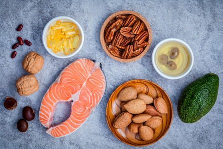 unsaturated: Selection food sources of omega 3 and unsaturated fats. Super food high omega 3 and unsaturated fats for healthy food. Almond ,pecan ,hazelnuts,walnuts ,olive oil ,fish oil ,salmon and avocado on stone background .