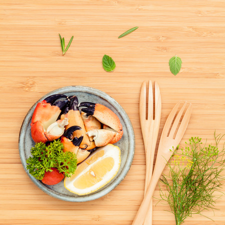 aquatic herb: Fresh steamed red crabs leg in bowl . Red crabs leg with ingredients. Steamed red crabs leg with herbs Fennel ,parsley,rosemary,lemon and mint with fork on wooden cutting board.