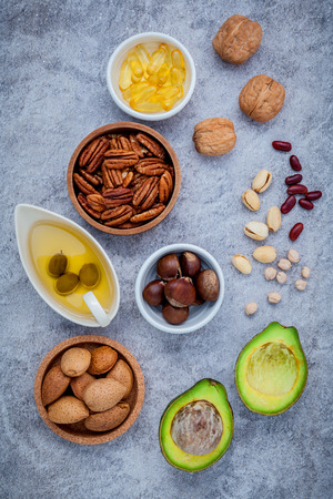 unsaturated: Selection food sources of omega 3 and unsaturated fats. super food high omega 3 and unsaturated fats for healthy food. Almond ,pecan ,hazelnuts,walnuts ,olive oil ,fish oil and avocado on stone background .