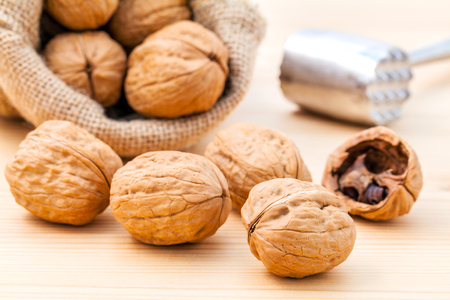 Walnuts kernels and whole walnuts on wooden background. Stock Photo