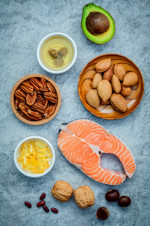 Almond ,pecan ,hazelnuts,walnuts ,olive oil ,fish oil ,salmon and avocado on stone background Banco de Imagens