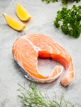 finocchio: Fresh salmon fillet slice on dark stone background with herbs fennel ,sage ,rosemary thyme,parsley and lemon Archivio Fotografico