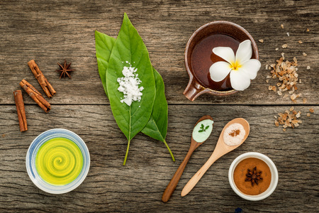 Avocados  leaves with nature spa ingredients dried indian bael ,cinnamon powder ,cinnamon sticks ,aromatic oil ,star anise  and sea salt on rustic background. Stock Photo