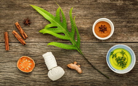 resort life: Branch of fern leaves with nature spa ingredients dried indian bael ,herbal compress ball,turmeric,cinnamon powder ,cinnamon sticks ,aromatic oil and star anise on rustic background.