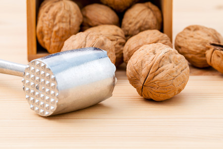 Walnuts kernels and whole walnuts on wooden background. Whole and chopped walnuts on wooden background. Walnuts kernels and nutcracker. Selective focus depth of field.