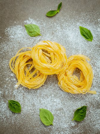 Italian food concept pasta with sweet basil with flour setup on concrete background. Homemade tagliatelle. Raw pasta on the concrete background. Food background top view .