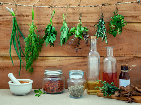 Assorted herb bundles hanging parsley ,sage,rosemary, dill,spring onion ,basil ,oregano and thyme for seasoning and cooking concept with oil flavored and mortar on rustic old wooden background.