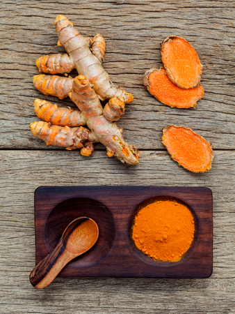 curcumin: Alternative ingredients for skin care. Homemade scrub curcumin powder and curcumin roots set up on old wooden background.