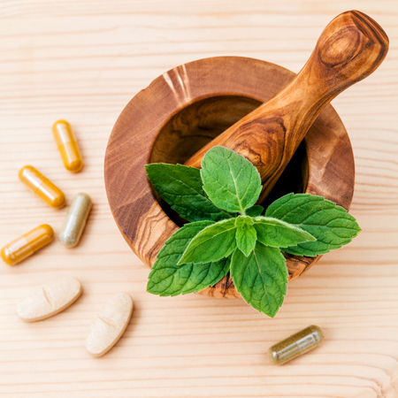 Fresh  peppermint leaves in olive wood mortar  and capsule of herbal medicine . Alternative health care concept setup on wooden background.