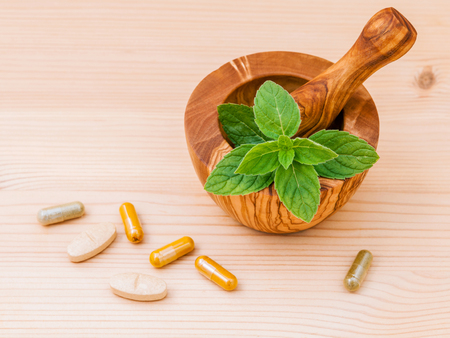 Fresh  peppermint leaves in olive wood mortar and capsule of herbal medicine Stock Photo