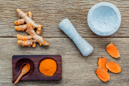 curcumin: Homemade scrub curcumin powder and curcumin roots with white mortar set up on old wooden background.