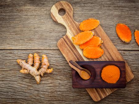 Eigengemaakt schrob curcumin poeder en curcumin wortels met scherpe raadsopstelling op oude houten achtergrond. Stockfoto