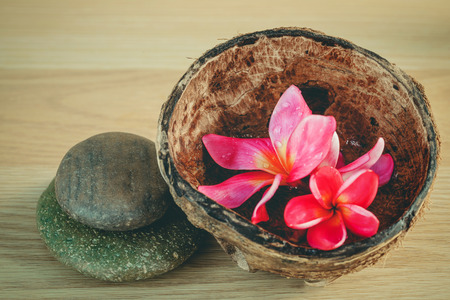 Aromatic oil in the coconut shell with Spa stones and frangipani flower . Toned photography  and selective focus shallow depth of field.