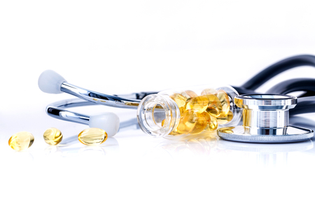 Fish oil capsules in bottle with stethoscope isolate on white background.