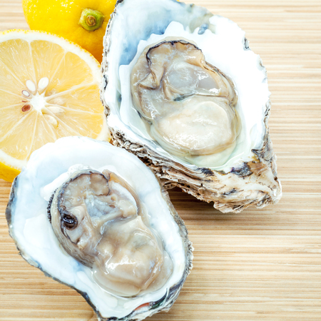 Fresh Oysters with lemon on  wooden background. Opened Oysters with selective focus on wooden texture . Stock Photo