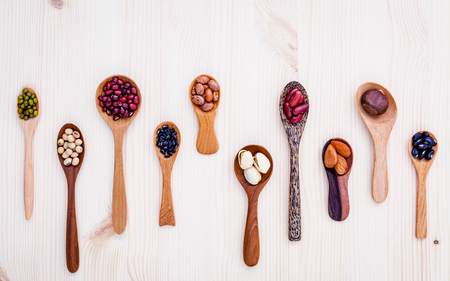 Assortment of beans and lentils in wooden spoon set up on wooden background. mung bean,soybean, red kidney bean , black bean ,red bean ,almonds ,pistachio,chestnut and brown pinto beans . Stock Photo