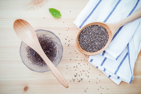 Nutritious chia seeds in glass bowl with wooden spoon for diet food ingredients setup on wooden background