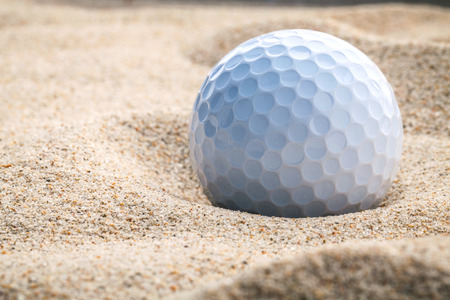 drawback: Close up golf ball in sand bunker Stock Photo