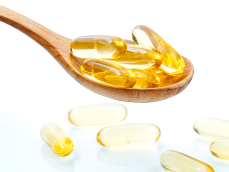 Spoonful of gel capsules of omega 3. Close up capsules fish oil in wooden spoon