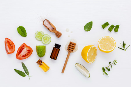 Homemade skin care and body scrubs with natural ingredients aloe vera ,lemon,cucumber ,himalayan salt ,tomato,mint ,lime slice,rosemary and honey set up on white wooden background with flat lay.