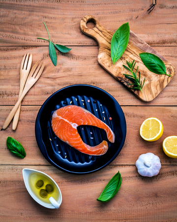 Raw salmon fillet in the black plate with ingredients olive oil ,himalayan salt, and herbs sweet basil ,fennel ,sage ,rosemary ,garlic ,pepper and lemon  on wooden background .