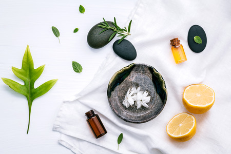 herbalism: Alternative medicine and aromatherapy bottle of essential oil with fresh herbal sage, rosemary, lemon and peppermint setup with flat lay on white wooden table.