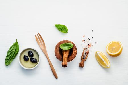 himalayan salt: Sweet basil vinaigrette dressing ingredients on white wooden background with flat lay. Fresh sweet basil leaves, lemon, olive oil and black olive, himalayan salt, pepper.