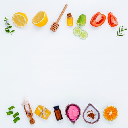 Zelfgemaakte huidverzorging en lichaam scrubs met natuurlijke ingrediënten Aloë vera, citroen, komkommer, Himalaya zout, tomaat, munt, limoen slice, rozemarijn en honing opgezet op witte houten achtergrond met plat lag.