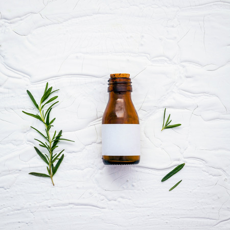 herbalism: Fresh branch of rosemary  with bottle essential oil setup on white wooden table. Stock Photo