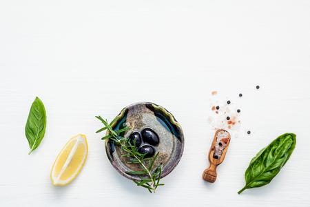 Sweet basil vinaigrette dressing ingredients on white wooden background with flat lay  Fresh sweet basil leaves, lemon, olive oil and black olive, himalayan salt, pepper .