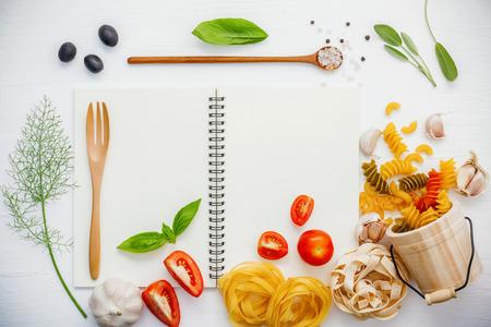 Verschillende pasta elleboog macaroni, fusilli, fettucini met ingrediënten tomaat, basilicum, venkel, salie bladeren, zwarte olijven, himalayazout, peper en knoflook setup op witte notebook Stockfoto